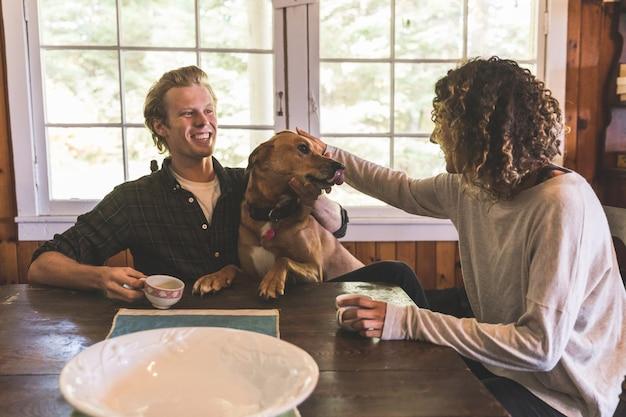 Paare, die mit einem hund in einer kabine spielen Premium Fotos