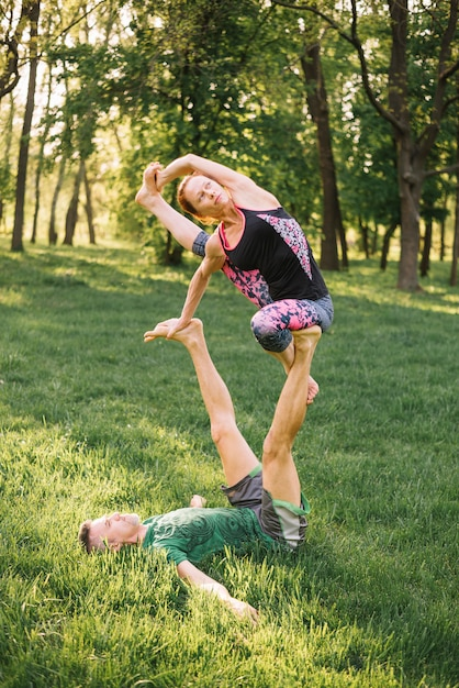 Paare, die muskel beim handeln von acro yoga balancieren und ausdehnen Kostenlose Fotos