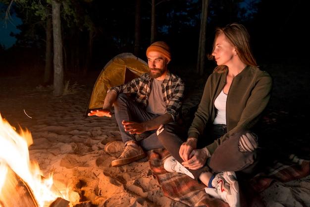 Paare, die nachts durch ein lagerfeuer aufwärmen Kostenlose Fotos