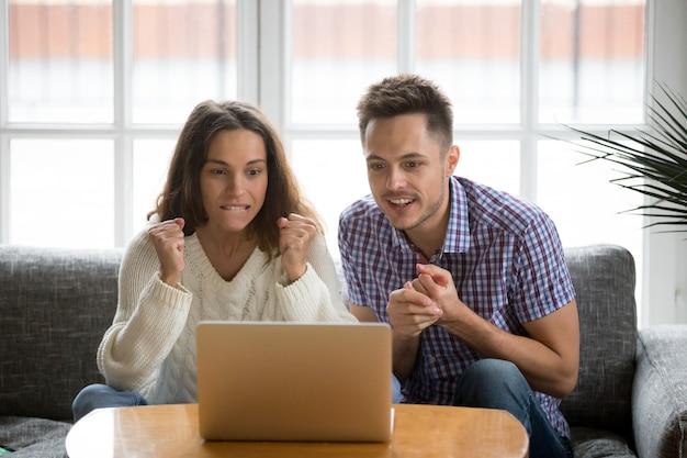 Paare, die online aufpassendes match des unterstützenden teams des laptopschirmes betrachten Kostenlose Fotos