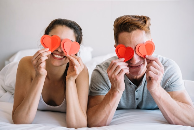 Paare, die papierherzen auf augen halten Kostenlose Fotos