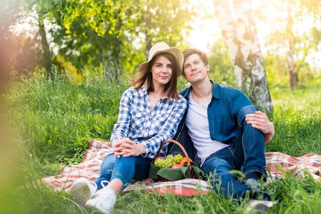 Paare, die reizendes picknick auf lichtung haben Kostenlose Fotos