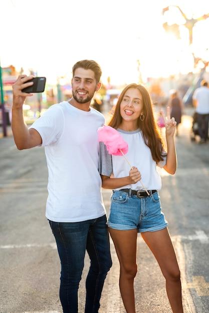 Paare, die selfie mit zuckerwatte nehmen Kostenlose Fotos