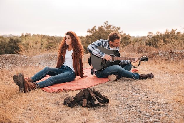 Paare, die sich draußen nahe bei einem lagerfeuer entspannen Kostenlose Fotos