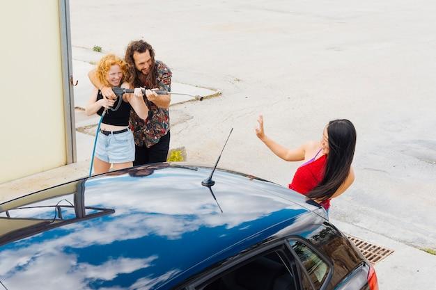 Paare, die spaß an der autowäsche haben Kostenlose Fotos