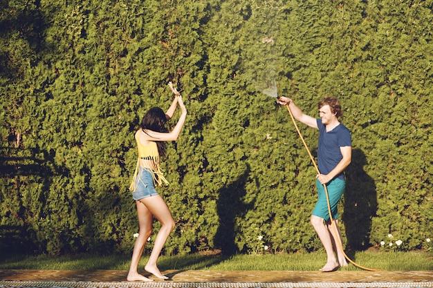 Paare, die spaß haben, gießen sich mit gartenschlauch Kostenlose Fotos