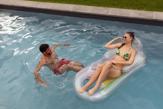Paare, die spaß zusammen im swimmingpool haben Kostenlose Fotos