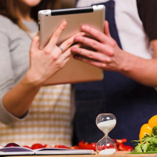 Paare, die tablette verwenden, während sanduhr eingeschaltet ist Kostenlose Fotos
