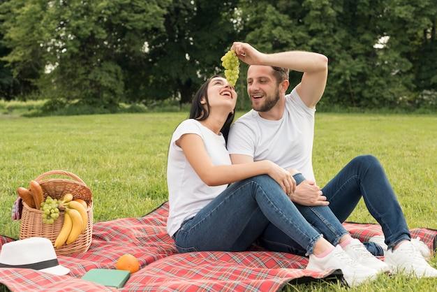 Paare, die trauben essen, legen eine picknickdecke herein Kostenlose Fotos