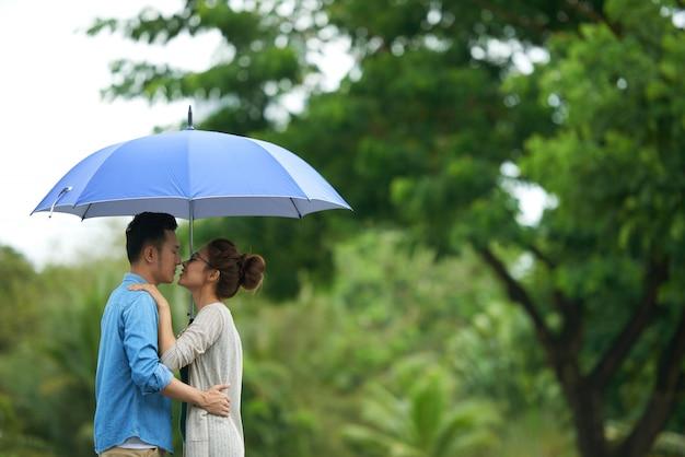 Paare, die unter regenschirm küssen Kostenlose Fotos