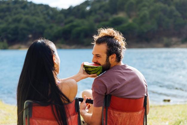 Paare, die wassermelone auf flussufer essen Kostenlose Fotos