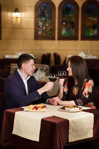 Paare, die weingläser in einem luxusrestaurant rösten. Premium Fotos
