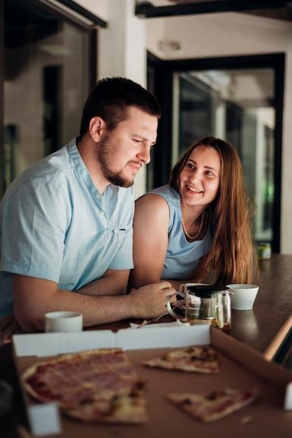 Paare, die zu hause kühlen und und pizza essen Kostenlose Fotos