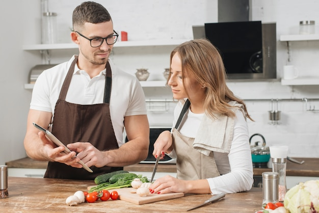 Paare, die zu hause mit tablette kochen Kostenlose Fotos