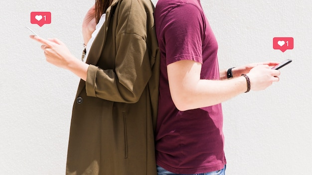 Paare, die zurück zu rückseite unter verwendung des mobiltelefons mit liebesmitteilungsikonen gegen wand stehen Kostenlose Fotos