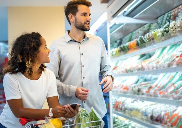 Paare, die zusammen an einem supermarkt kaufen Premium Fotos