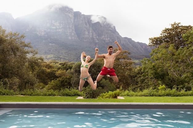 Paare, die zusammen in den swimmingpool springen Kostenlose Fotos