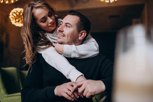 Paare, die zusammen innerhalb eines cafés umarmen und sitzen Kostenlose Fotos