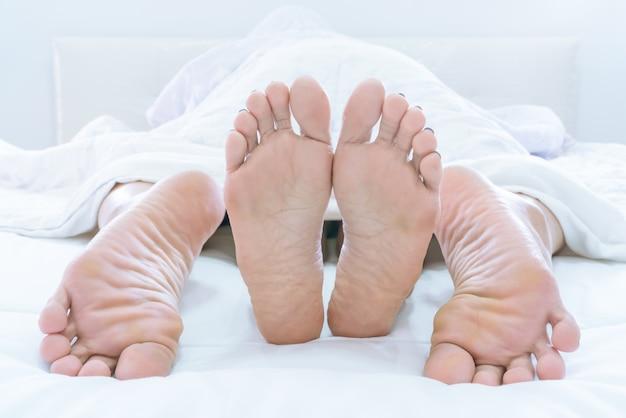 Paare füße, die unter duvet oder blanket herausragen, machen die liebe zu hause im schlafzimmer Premium Fotos