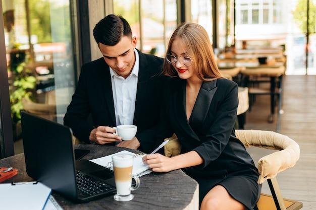 Paare im café, das am laptop während des abendessens arbeitet. - bild Premium Fotos