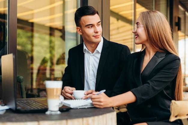 Paare im café, das am laptop während des abendessens arbeitet und sich schaut. - bild Premium Fotos