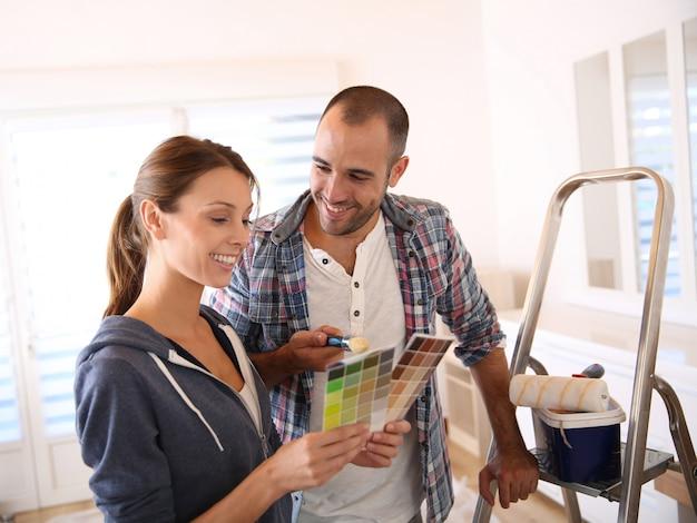Paare im neuen haus, das farbe für wände wählt Premium Fotos