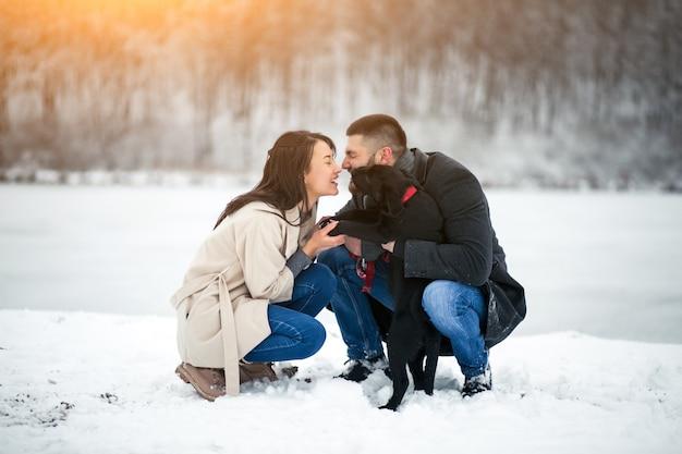 Paare im winter in der straße mit hund Kostenlose Fotos