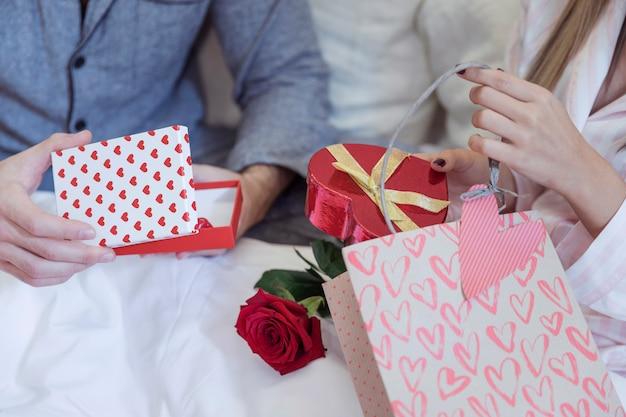 Paare in den pyjamas, die auf bett mit geschenken sitzen Kostenlose Fotos