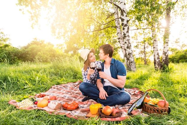 Paare in der liebe, die auf wiese picknickt Kostenlose Fotos