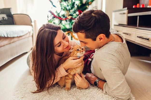 Paare in der liebe, die durch weihnachtsbaum liegt und zu hause mit katze spielt. mann und frau entspannen Premium Fotos