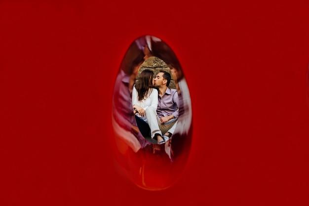 Paare in der liebe küssen. junges paar in der liebe, die auf dem boden sitzt und küsst. liebesgeschichte Kostenlose Fotos