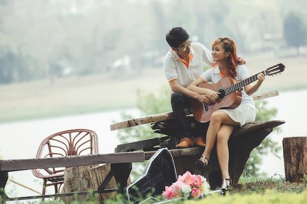 Paare in der liebe mit dem spielen der gitarre an der natur Kostenlose Fotos