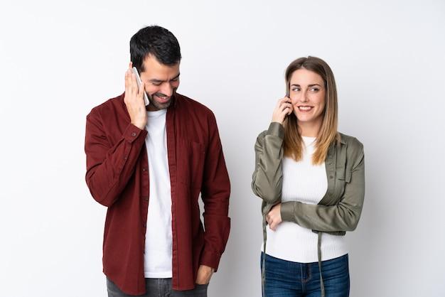 Paare in valentine day über lokalisierter wand sprechend mit mobile Premium Fotos