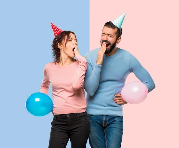 Paare mit den ballonen und geburtstagshüten, die mund mit der hand gähnen und bedecken. Premium Fotos