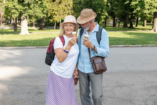 Paare mit der eiscreme in der hand, die durch park geht Kostenlose Fotos