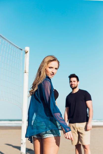 Paare nähern sich dem volleyballnetz, das kamera betrachtet Kostenlose Fotos