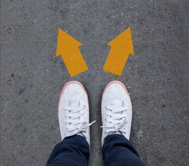 Paare schuhe, die auf einer asphaltstraße mit zwei pfeilen stehen Premium Fotos