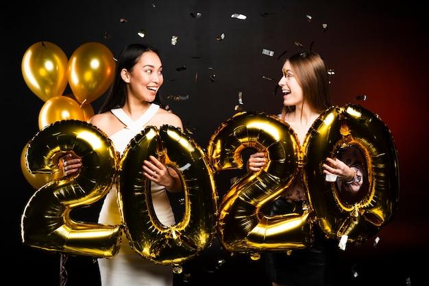 Paare von den freunden, die einander party der neuen jahre betrachten Kostenlose Fotos