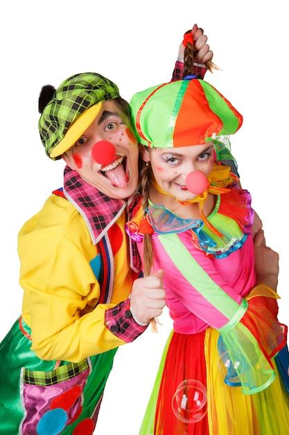 Paare von den glücklichen clowns lokalisiert auf weißem hintergrund Premium Fotos