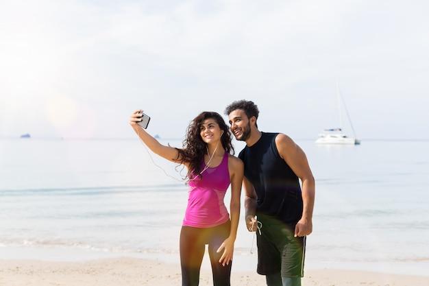 Paare von den läufern, die selfie-foto beim auf strand zusammen rütteln machen Premium Fotos