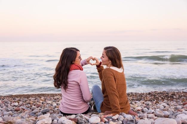 Paare von den lesbischen mädchen, die auf dem strand zusammen aufpasst und einen schönen sonnenuntergang genießt sitzen Premium Fotos