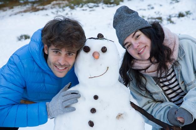 Paare von den liebhabern, die im schnee mit einem schneemann genießen. Premium Fotos