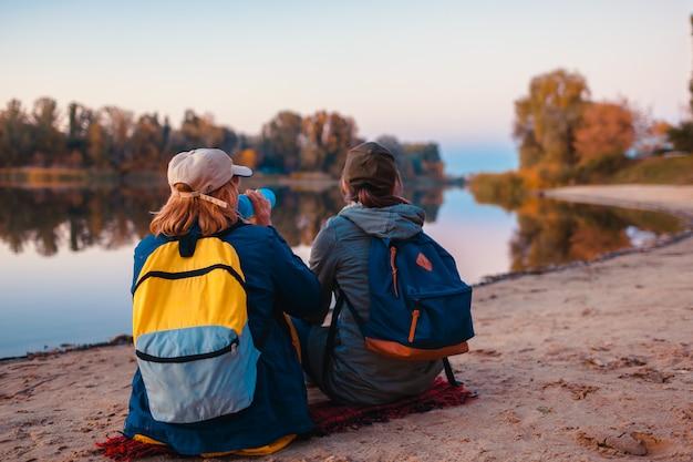 Paare von touristen mit den rucksäcken, die durch trinkwasser der herbstflussbank sich entspannen und rest haben Premium Fotos