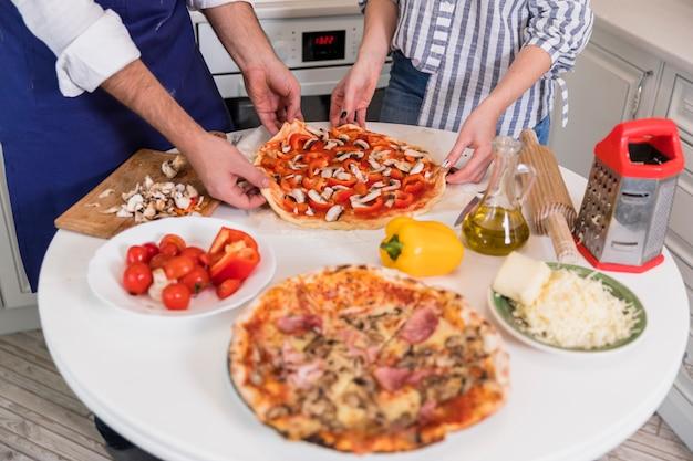 Paarholdingpizza mit pilzen und gemüse Kostenlose Fotos