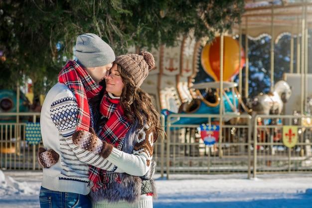 Paarumarmungen im winterpark durch karussell. Premium Fotos