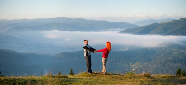 Paarwanderer, die hände anhalten und auf einem hügel sich gegenüberstellen Premium Fotos