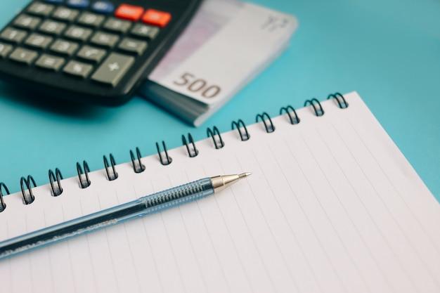 Packung mit euro-banknoten und einem taschenrechner auf blauem grund Premium Fotos