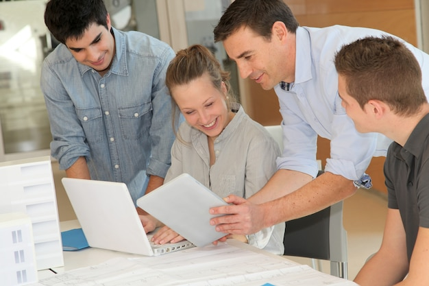 Pädagoge mit studenten in der architektur, die an elektronischer tablette arbeitet Premium Fotos