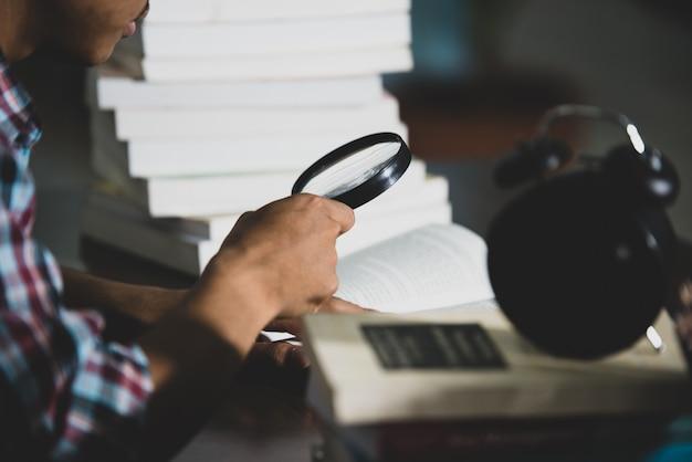 Pädagogisches thema: nahaufnahme-student, der durch eine lupe schaut, um zu buchen Kostenlose Fotos