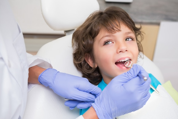 Pädiatrischer zahnarzt, der zähne eines kleinen jungen im zahnarztstuhl überprüft Premium Fotos